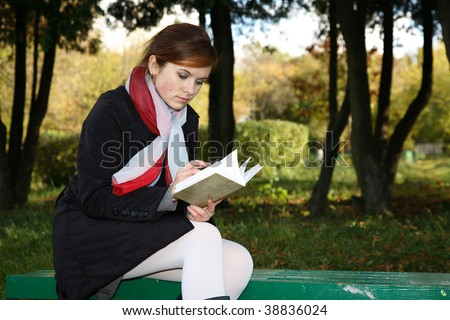 The girl sits on a bench in steam and reads the book