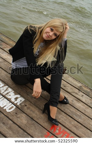 The girl sits on a pier