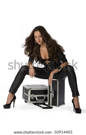 The girl sits on a suitcase - stock photo
