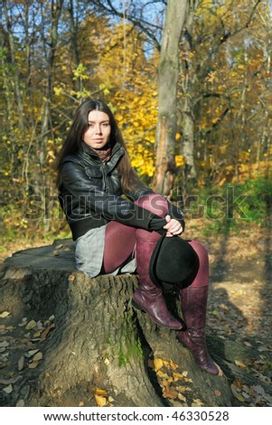 The girl sits on stump in wood