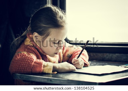 The girl sitting at a desk writing in train. - stock photo