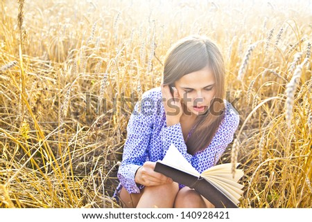 The girl sitting on a grass, reading a book - stock photo
