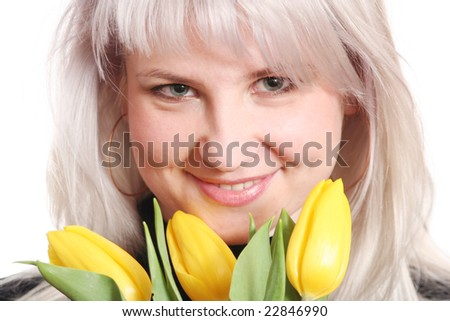 The girl smiles with a bouquet of yellow tulips in hands