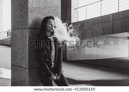 The girl smokes an electronic cigarette