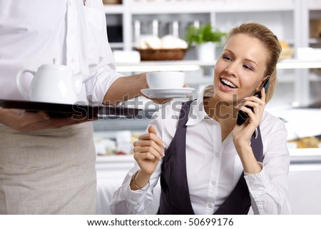 The girl speaking on the phone waits a coffee cup in cafe - stock photo