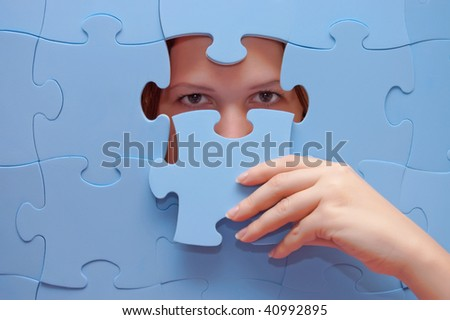 The girl spies through a blue puzzle - stock photo