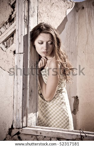 The girl standing near a window of the destroyed house