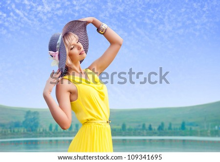 The girl straightens his hat against the blue cloudy sky - stock photo