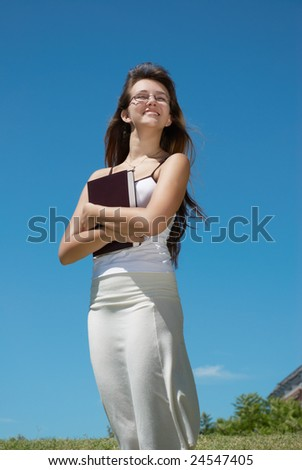 The girl student with book against sky - stock photo