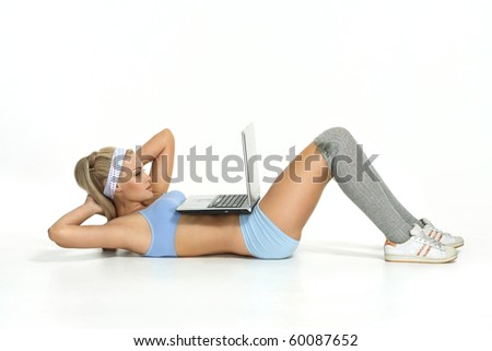 The girl swings a press and looks in the laptop on the floor - stock photo