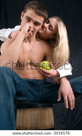 The girl tempts the guy with an apple on a black background - stock photo