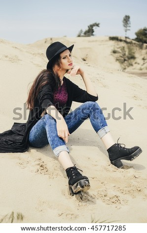 the girl the brunette with a round black hat, poses. On her the long jacket and an undershirt are put on