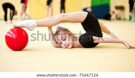 The girl the gymnast trains in a gym - stock photo