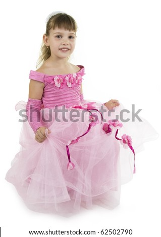 The girl the princess in a pink dress sits opposite to a white background