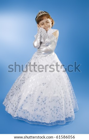 The girl the princess in a white dress sits opposite to a blue background - stock photo