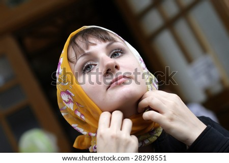 The girl ties a kerchief round one's head - stock photo