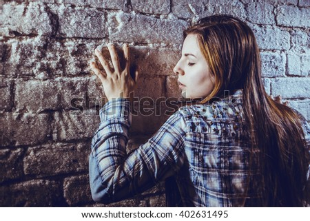 The girl touches the frozen brick wall - stock photo