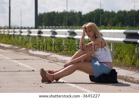 The girl, travelling  hitch-hiking, sits on a flank.