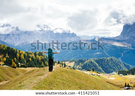 The girl with a backpack standing on the edge of the slope at full breath in the mountains - stock photo