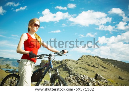The girl with a bicycle against mountains - stock photo