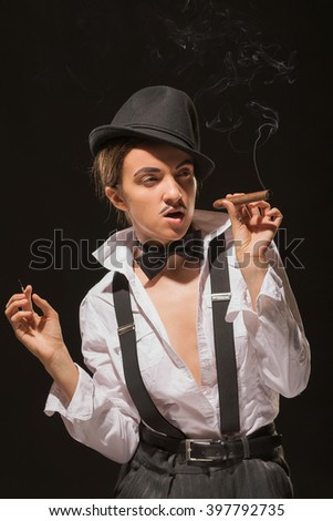 The girl with a cigar in a men's suit with a tie a butterfly, against a dark background. (with rigid light and shadows)  - stock photo
