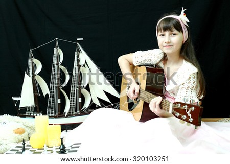 The girl with a guitar on a black background - stock photo