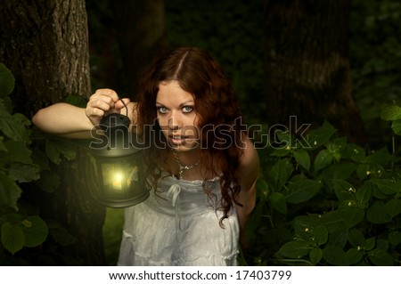 The girl with a lantern restlessly looks on a background of a twilight wood - stock photo