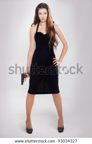 The girl with a pistol costs having lowered hands - stock photo