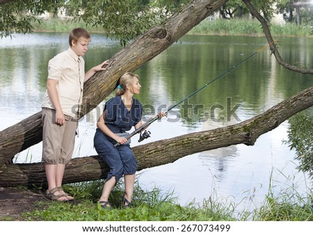 The girl with a rod and the guy looks at it - stock photo