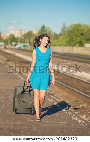 The girl with a suitcase goes along a railway way - stock photo