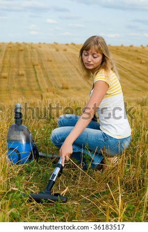 The girl with a vacuum cleaner cleans hay field - stock photo