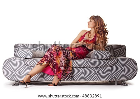 The girl with a wine glass on a sofa - stock photo