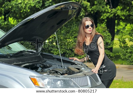The girl with a wrench is near the motor vehicle with the open hood - stock photo