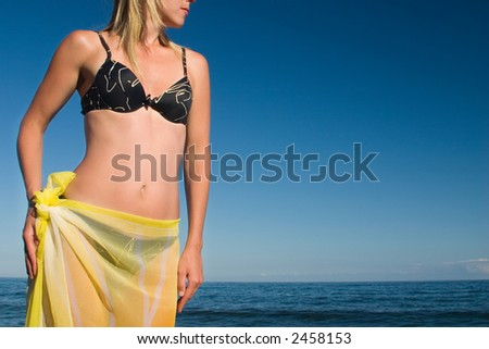 The girl with a yellow scarf on a sea background - stock photo