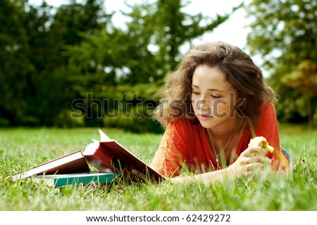 The girl with books lying on a grass - stock photo