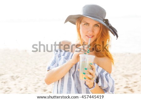 the girl with drink sunbathes on the beach