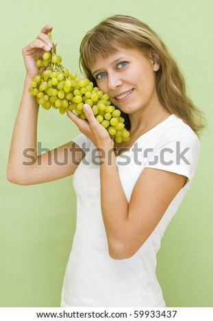 The girl with grapes on a green background - stock photo