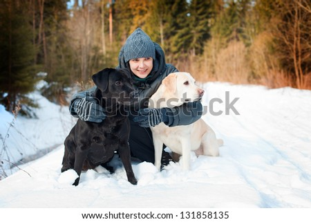 The girl with Labradors on walk in the winter wood