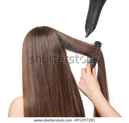 The girl with long hair, comb and a hairdryer in the hands of the hairdresser isolated on white background.