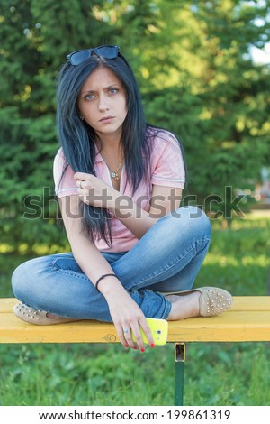 The girl with phone sits on a bench - stock photo