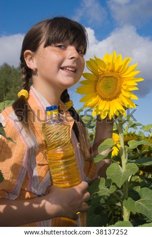 The girl with sunflower and bottle of oil on field