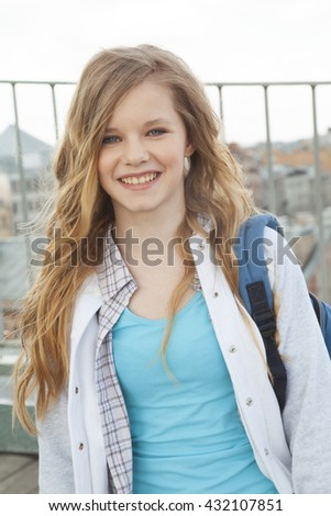 the girl with the backpack is standing on the roof and charming smiles