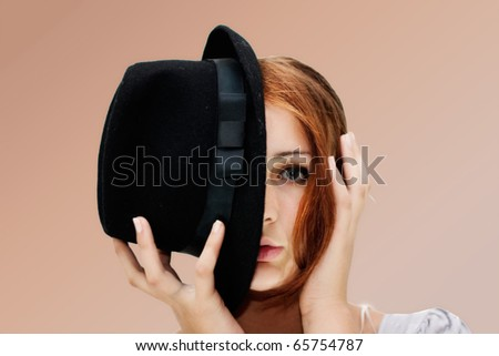 The girl with the black hat covering the half of the face, isolated on a white background