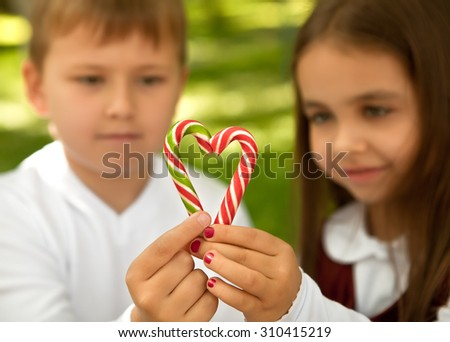 The girl with the boy put the figure of a heart of sweet caramel - stock photo