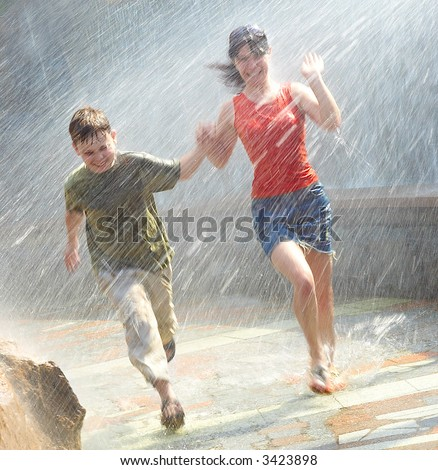 The girl with the boy run under a down-pour rain - stock photo
