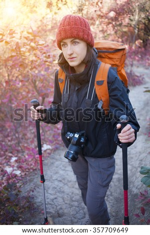 The girl with the camera and the backpack goes on the trail in a beautiful forest.