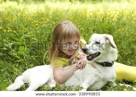 The girl with the dog lying on the grass in the summer.