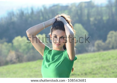 the girl with the green dress touches her hair in a natural - stock photo