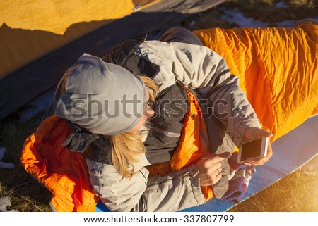 The girl with the phone lying in a sleeping bag on the nature. - stock photo