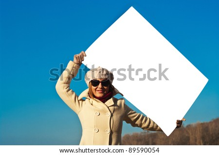 The girl with the poster against the sky - stock photo